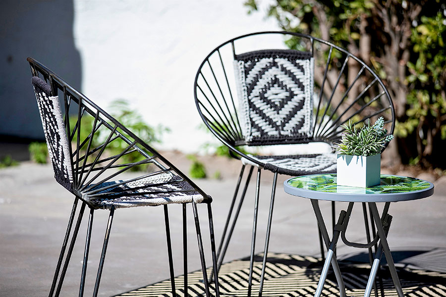 Mary Ln Day 26 two chairs with geometric designs in black and white outside in a backyard